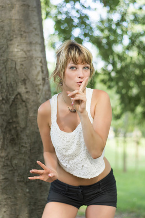 shushing: Pretty young woman in shorts and a t-shirt making a shushing gesture, asking for silence or to keep a secret, as she holds her finger to her lips in summer woodland
