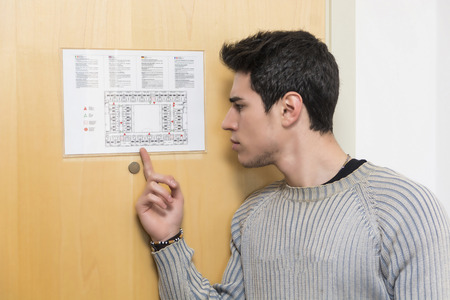 floorplan: Handsome young man in hotel pointing at printed floorplan