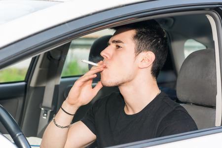 joven fumando: Hombre Joven fumar cigarrillo mientras conducen un coche