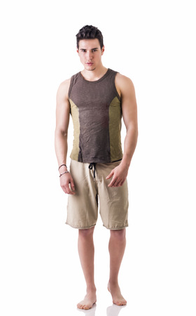 Full length shot of handsome guy wearing stylish half shorts and t-shirt isolated in white