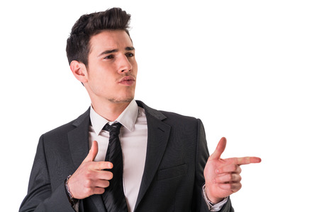 confidently: Young businessman confidently pointing fingers to a side, wearing suit isolated in white background Stock Photo