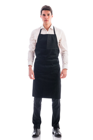 Full length shot of young chef or waiter posing, wearing black apron and white shirt isolated on white background