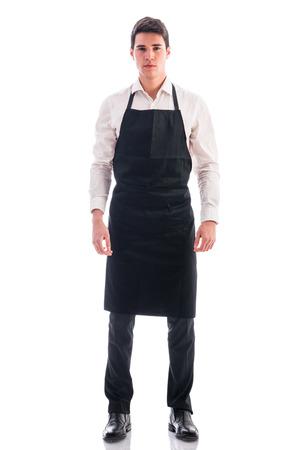 Długie strzał młody kucharz lub kelner pozowania, ma na sobie czarny fartuch i białą koszulę na białym tle