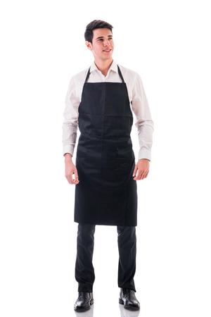 delantal: Tiro integral de joven chef o posando camarero, vestido con delantal negro y camisa blanca aislada en el fondo blanco