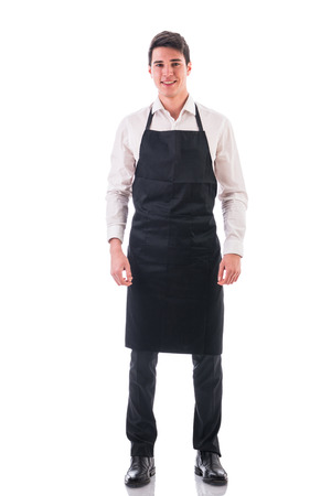uniforms: Full length shot of young chef or waiter posing, wearing black apron and white shirt isolated on white background