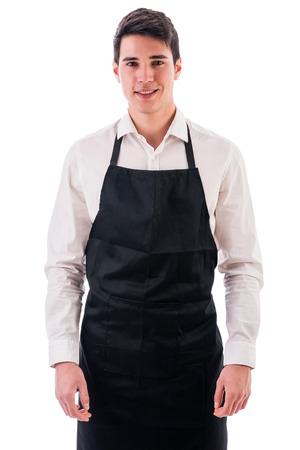 delantal: Joven chef o posando camarero, vestido con delantal negro y camisa blanca aisladas sobre fondo blanco