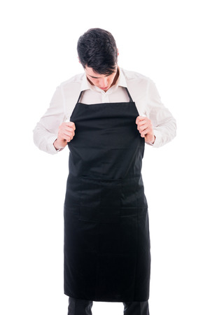 apron: Young chef or waiter posing, wearing black apron and white shirt isolated on white background Stock Photo