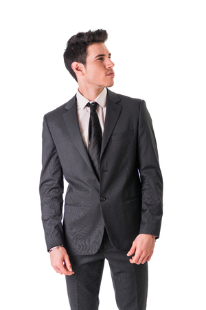 confidently: Young businessman confidently posing and looking to a side, wearing suit isolated in white background