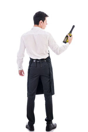 Back of attractive young chef holding green champagne bottle isolated in white