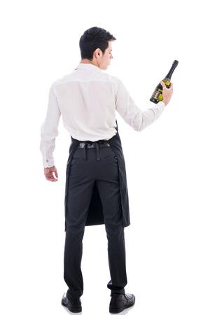meseros: Parte posterior de la atractiva joven chef sosteniendo la botella de champagne verde aislado en blanco