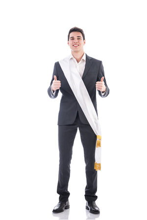 sash: Young businessman confidently posing wearing winning ribbon or sash, showing thumbs up isolated in white background Stock Photo