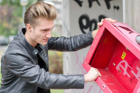 vandal: Handsome young male vandal breaking public property, pulling down metal object Stock Photo