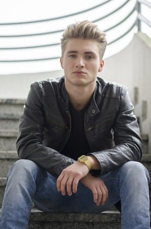 Attractive blond young man wearing black leather jacket and jeans sitting on stairs outside photo