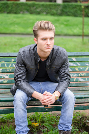 Handsome blond young man sitting on green, wooden park bench photo