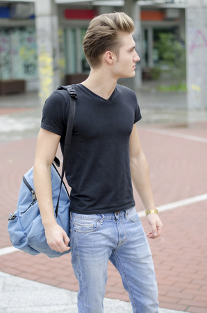 back pack: Attractive young man wearing black T-shirt and jeans with back pack standing outside