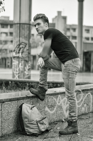 ruck sacks: Attractive young man wearing black T-shirt and jeans with back pack standing outside