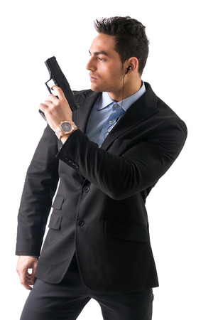 undercover agent: Elegant man with gun, dressed as a spy or secret agent, with earphones, isolated on white