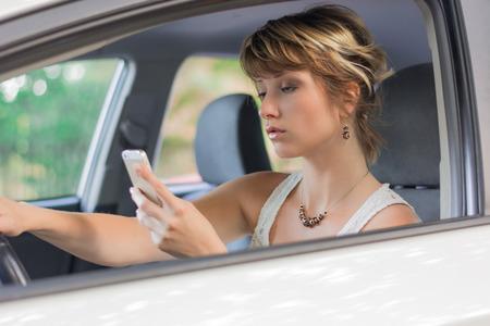 気を取られて、車を運転している間携帯電話を使用して魅力的な金髪の若い女性 写真素材