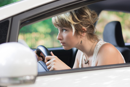 leaning forward: Profile of Young Woman Learning to Drive a Car, Leaning Forward and Peering Through Car Windshield Stock Photo