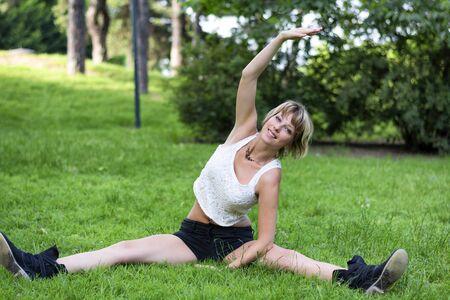 beine spreizen: Gesunde Junge Hübsche Frau macht eine Übung ausdehnt Außen am Grasboden Alleine