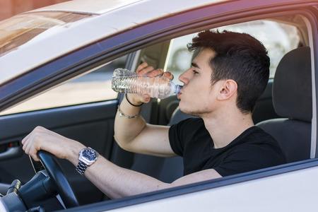 tomando agua: Hombre o adolescente joven hermoso que conduce el coche y el agua potable de la botella de pl�stico Foto de archivo