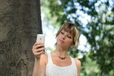 tanktop: Attractive blonde young woman outdoors taking photo or selfie with cell phones camera