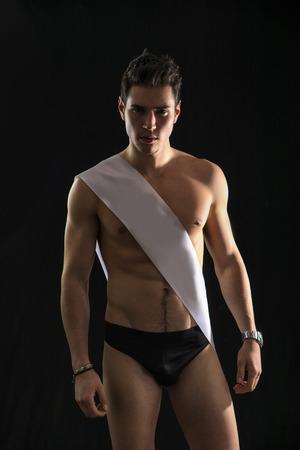 sash: Handsome shirtless guy wearing black underwear and winning ribbon or sash isolated on black Stock Photo