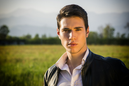 Handsome young man at countryside, in front of field or grassland, wearing white shirt and jacket, looking at camera