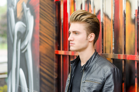 blond haired: Profile of attractive blond haired young man standing against graffiti wall, looking to a side Stock Photo