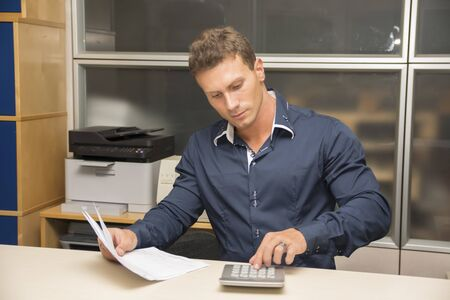 Handsome young man working in office at his desk using calculator photo