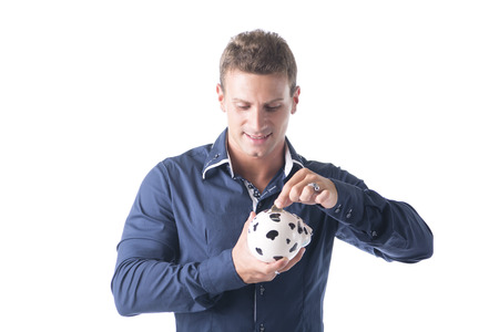 piggybank: Young handsome man putting coin in piggy-bank, isolated on white background