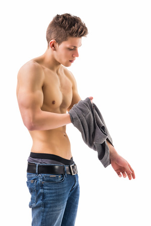 undressing: Attractive fit athletic trendy young man undressing, taking off t-shirt, isolated on white