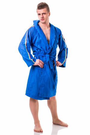 bath gown: Handsome young man wearing blue bathrobe, isolated on white background Stock Photo