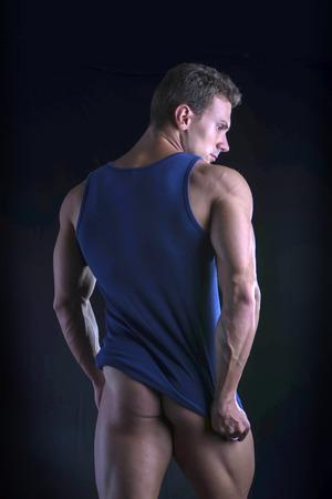 nalga: Detrás del hombre atlético joven que tira hacia abajo techo del doble fondo en el torso musculoso rasgado, aislado en fondo oscuro