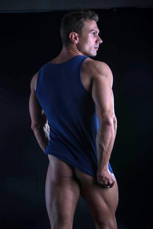 hintern: Zurück von jungen sportlichen Mann Herunterziehen tanktop auf riss muskulösen Oberkörper, isoliert auf dunklem Hintergrund