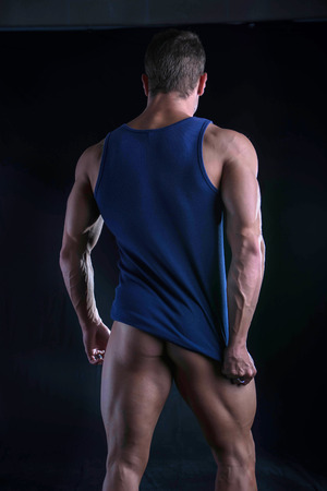 tanktop: Back of young athletic man pulling down tanktop on ripped muscular torso, isolated on dark background Stock Photo