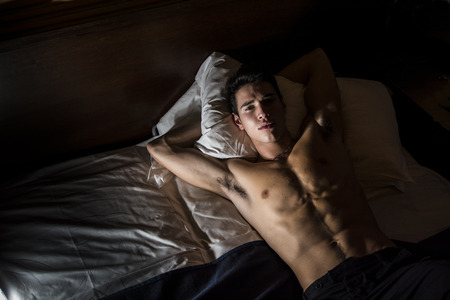 cuerpo hombre: Hermoso hombre sin camisa atlética joven que pone en la cama en la noche mirando a la cámara, visto desde arriba