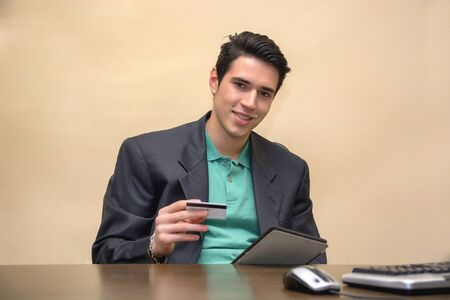 entering information: Young man in office with tablet PC and credit card buying from ecommerce website or checking financial transactions