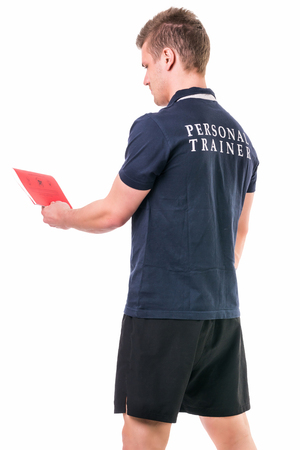 personal trainer: Handsome young personal trainer with clipboard, standing isolated on white background
