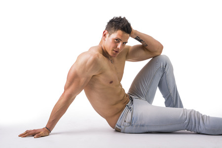 hunk: Handsome young bodybuilder laying down on the floor, showing ripped abs, muscular pecs, arms Stock Photo