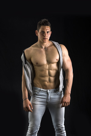 Confident, attractive young man with open vest on muscular torso, ripped abs and pecs. Isolated on black photo