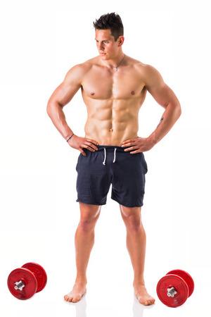 Stattlicher muskulöser mit nacktem Oberkörper junger Mann mit Hanteln, isoliert auf weiß, voller Länge gedreht