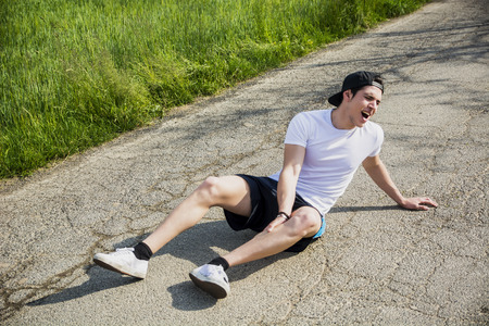 Handsome young man injured while running and jogging on road in the country in a sunny day, wearing white shirt and baseball cap