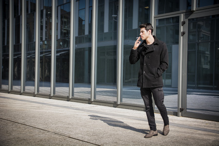 Handsome stylish young man smoking outside in urban setting, looking away