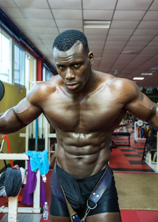topless model: Hunky muscular black bodybuilder working out in gym, exercising with weights