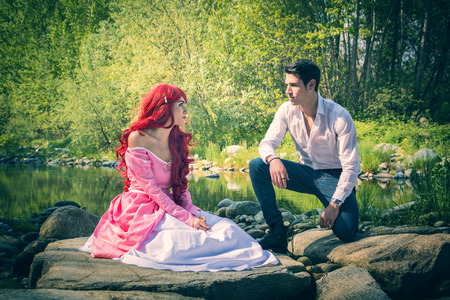 Romantic Fairy Tale Couple Sitting on Rocks at River Side in Peaceful Idyllic Setting, Prince and Princess Gazing at Each Other photo