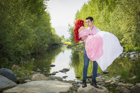 princesa: Romántico cuento de hadas Pares que se sientan en las rocas en River Side en el pacífico entorno idílico, el príncipe y la princesa mirando el uno al otro