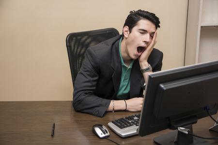 empleados trabajando: Cansado joven hombre de negocios aburrido sentado en su escritorio frente a su bostezo computadora, con la barbilla apoyada en la mano y los ojos cerrados, en su oficina
