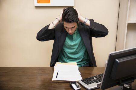preoccupied: Preoccupied, worried, desperate young male worker staring at computer screen in his office Stock Photo