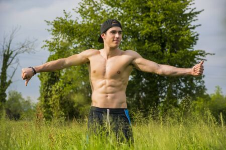 stupid body: Shirtless young man doing funny pose standing with outstretched arms in the sunshine at countryside